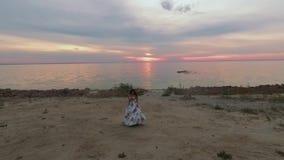 Młoda dziewczyna w długiej sukni chodzi wzdłuż brzeg Strzelający na trutniu zbiory wideo