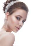 Młoda dziewczyna w delikatnym ślubnym wizerunku z diademem na jej głowie Piękny model w wizerunku panna młoda na biali odosobneni Zdjęcia Royalty Free