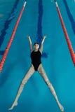 Młoda dziewczyna w gogle i nakrętki dopłynięcie w z tyłu błękitne wody basenu Sporty kobieta relaksuje w błękitne wody Obraz Stock