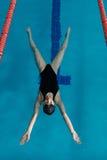 Młoda dziewczyna w gogle i nakrętki dopłynięcie w z tyłu błękitne wody basenu Sporty kobieta relaksuje w błękitne wody Zdjęcie Stock