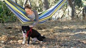 Młoda Dziewczyna w hamaku Bawić się z psem Zdjęcia Stock