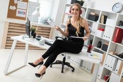 Młoda dziewczyna w hełmofonach siedzi na biurku w biura i chwytów dokumentach w rękach Zdjęcia Royalty Free