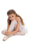 Młoda dziewczyna w jej tana dojechania odzieżowym puszku dotykać jej stopę Zdjęcia Stock