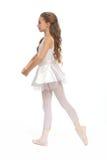 Młoda dziewczyna w jej tana dojechania odzieżowym puszku dotykać jej stopę Zdjęcie Stock