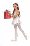 Młoda dziewczyna w jej tana dojechania odzieżowym puszku dotykać jej stopę z prezentami w ręce Zdjęcia Stock