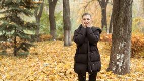 Młoda dziewczyna w jesień parku w czarnej kurtce obrazy stock