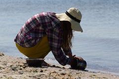 Młoda dziewczyna w kapeluszu od słońca obsiadania na haunches i obmyć dęciaka skala łasowaniu Metali naczynia kulinarny zioło obrazy stock