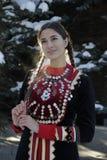 Młoda dziewczyna w krajowym kostiumu w zima lesie fotografia stock