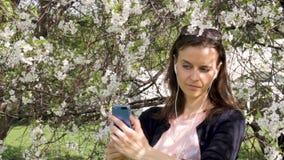 Młoda dziewczyna w kwitnących drzewach bierze selfie zbiory wideo