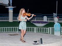 Młoda dziewczyna w lato wieczór bawić się dla przechodni na skrzypce na nabrzeżu Nahariya, Izrael Zdjęcie Royalty Free