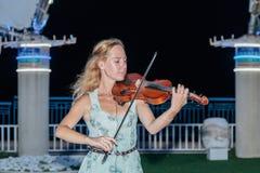 Młoda dziewczyna w lato wieczór bawić się dla przechodni na skrzypce na nabrzeżu Nahariya, Izrael Obrazy Royalty Free
