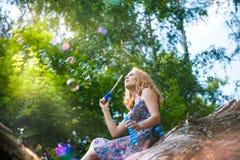 Młoda dziewczyna w lesie bawić się z mydlanymi bąblami Obrazy Royalty Free