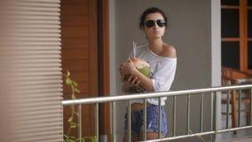 Młoda dziewczyna w okularach przeciwsłonecznych w ranek pozyci z koksem i pić swój sok przez słoma elegancki zdjęcie wideo