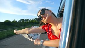 Młoda dziewczyna w okularach przeciwsłonecznych z szalikiem w ona ręki opiera z nadokiennego retro samochodu i raduje się podróż  zbiory