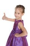 Młoda dziewczyna w purpurowej sukni trzyma jej kciuk up fotografia stock