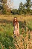 Młoda dziewczyna w retro rocznik sukni z bieżącym włosy stoi w wysokiej trawie w światła słonecznego afterglow z walizką obraz stock