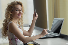 Młoda dziewczyna w sukni z kredytową kartą w ręce uśmiechniętej i patrzeje kamerę Obraz Royalty Free