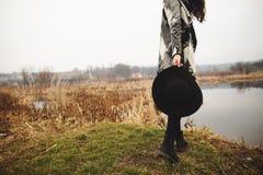 Młoda dziewczyna w szarym kardiganie trzyma kapelusz w ona ręki i pozy na brzeg jezioro zdjęcie stock