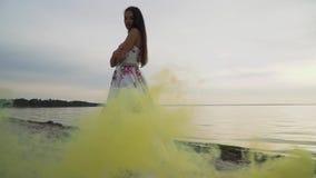 Młoda dziewczyna w wieczór sukni na tle dymne bomby zbiory wideo