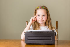Młoda dziewczyna wprawiać w zakłopotanie podczas gdy pracujący na starym maszyna do pisania fotografia stock