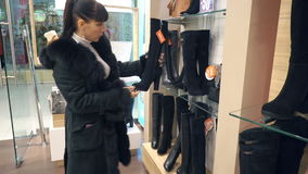 Młoda dziewczyna wybiera w butik zimy butach zbiory
