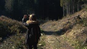 Młoda dziewczyna wycieczkowicz jest mknącym wideo piękny lasu krajobraz z rzeką na telefon komórkowy kamerze zbiory wideo