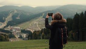 Młoda dziewczyna wycieczkowicz jest mknącym wideo piękny mglistej góry krajobraz na telefon komórkowy kamerze zdjęcie wideo