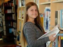 Młoda dziewczyna wyszukuje książki Obrazy Royalty Free