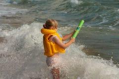 Młoda dziewczyna z żółtą kamizelką ratunkową Na brzeg z falami Wodna krócica zdjęcie royalty free