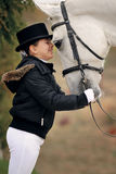 Młoda dziewczyna z białym dressage koniem Zdjęcie Royalty Free
