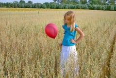 Młoda dziewczyna z czerwień balonem w banatce obraz stock
