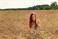 Młoda dziewczyna z czerwonym włosy ostrożnie przegląda ucho banatka na wiejskim polu zdjęcia royalty free