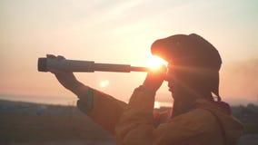 Młoda dziewczyna z długim ciemnym włosy w żółtej kurtki i kowbojskiego kapeluszu rzemiennych spojrzeniach w teleskop zdjęcie wideo