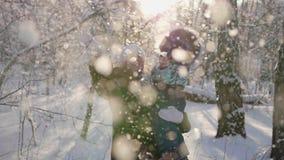 Młoda dziewczyna z dzieckiem bawić się w zima parku snowfall Zima słoneczny dzień Spacery w świeżym powietrzu zbiory wideo