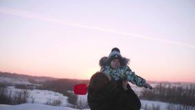 Młoda dziewczyna z dzieckiem bawić się w zima parku Spacery w świeżym powietrzu Zmierzch zbiory wideo