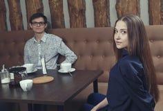 Młoda dziewczyna z facetem w kawiarni siedzi na leżanki połówce obracającej Zdjęcie Royalty Free