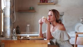 Młoda dziewczyna z filiżanką kawy lub herbatą na greckiej kuchni zbiory wideo