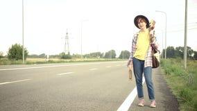Młoda dziewczyna z gitary przybyciem wzdłuż drogi zbiory wideo