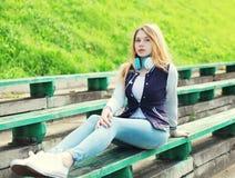 Młoda dziewczyna z hełmofonów siedzieć słucha muzyka w mieście Zdjęcia Royalty Free