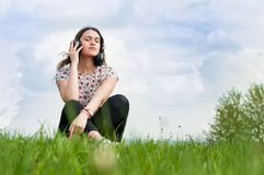 Młoda dziewczyna z hełmofonami na ona kierowniczy obsiadanie na trawie obrazy royalty free