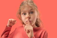 Młoda dziewczyna z jej palcem na jej usta na koralowym tle zdjęcie stock