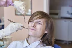 Młoda dziewczyna z krótkim ostrzyżeniem siedzi w dentysty ` s krześle Wyraz twarzy z horrorem i strachem ból od dentysty obraz royalty free