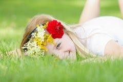 Młoda dziewczyna z kwiecistego wianku plenerowy ono uśmiecha się Zdjęcie Stock