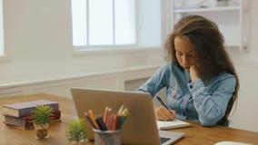 Młoda dziewczyna z laptopem robi pracie domowej Szkoły wyższa edukacja Zmęczony Żeńskiego ucznia studiowanie i używać w domu komp zdjęcie wideo