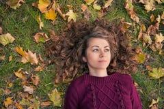 Młoda dziewczyna z liśćmi w jesieni Zdjęcia Royalty Free