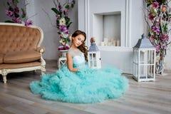 Młoda dziewczyna z niebieskimi oczami, uzupełniał i fryzura w luksusowej turkus sukni w studiu z kwiat dekoracją obraz stock