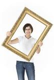 Młoda dziewczyna z obrazek ramą przed ona zdjęcia royalty free
