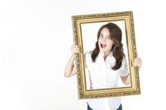 Młoda dziewczyna z obrazek ramą przed ona robi niemądrej twarzy zdjęcie stock