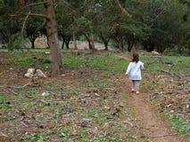 Młoda dziewczyna z odprowadzeniem w lesie z powrotem kamera zdjęcia stock