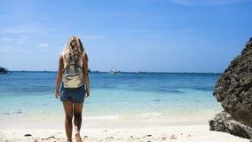 Młoda dziewczyna z pięknym włosy w kombinezonach z plecakiem iść na pięknej biel plaży z skałami zbiory